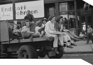 Children, recruited for farm work during the summer sit on the back of a truck.