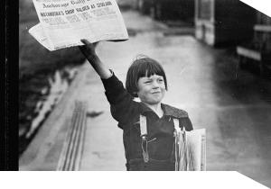 A newsboy holding up a newspaper
