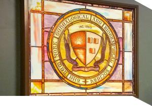 A stained glass window displaying the seal of the New York Genealogical and Biographical Society