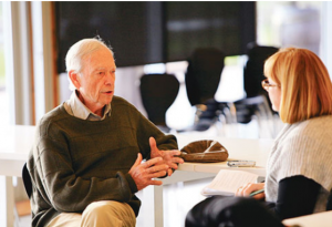 An older man being interviewed by a younger woman