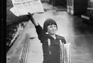 A newsboy holding up a newspaper